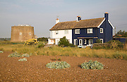 Martello tower and beach houses at coastal hamlet of Shingle Street, North Sea coast, Suffolk, England, UK