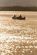 People in canoe paddling on river, Zambezi River, Zambia