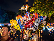 21 NOVEMBER 2015 - BANGKOK, THAILAND: A vendor who sells inflatable toys at the Wat Saket temple fair. Wat Saket is on a man-made hill in the historic section of Bangkok. The temple has golden spire that is 260 feet high which was the highest point in Bangkok for more than 100 years. The temple construction began in the 1800s in the reign of King Rama III and was completed in the reign of King Rama IV. The annual temple fair is held on the 12th lunar month, for nine days around the November full moon. During the fair a red cloth (reminiscent of a monk's robe) is placed around the Golden Mount while the temple grounds hosts Thai traditional theatre, food stalls and traditional shows.     PHOTO BY JACK KURTZ
