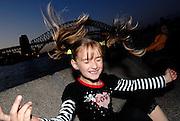 Child (6 years old) flicking hair in air, Sydney Harbour Bridge at sunset in background. Sydney, Australia