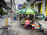22 AUGUST 2014 - BANGKOK, THAILAND:      A fruit seller on the sidewalk near Sukhumvit Soi 77. The Thai military junta, formally called the National Council for Peace and Order (NCPO), has ordered street vendors off of the sidewalks in an effort to bring order to Bangkok's chaotic sidewalks. Vendors have complained that the new regulations are hurting them economically but largely complied with the military orders.      PHOTO BY JACK KURTZ