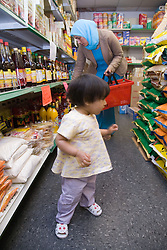 Mother and young daughter shopping in supermarket
