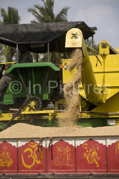 Combine harvester. Rice harvest, in a field near Hampi, Karnataka, India.