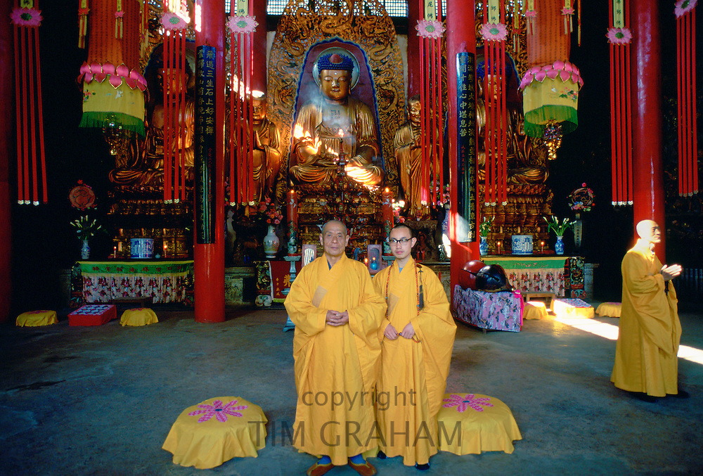 Buddhist monks in saffron coloured robes at the Buddhist Temple in Huating, Kunming, China
