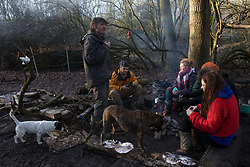 Harefield, UK. 19 January, 2020. Activists from Extinction Rebellion, Stop HS2 and Save the Colne Valley sit around a camp fire at the Colne Valley wildlife protection camp on the third day of a 'Stand for the Trees' event in the Colne Valley timed to coincide with tree felling work for HS2 in the area. Bailiffs acting for HS2 had been evicting activists from the camp for the past week and a half but it was retaken by activists seeking to protect the trees the previous. 108 ancient woodlands are set to be destroyed by the high-speed rail link.