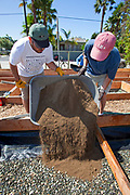 July 24, 2010. Laying down the soil for the final preparations of the planting beds at the Venice Community Garden. The Venice Garden broke ground in April, 2010. Soil tests revealed high levels of arsenic and lead because of previous uses which included a railroad line going through the lot. Steps were taken which included adding protective layers and adding new soil. Planting began in August and the first harvest was in October, 2010. Venice, California, USA