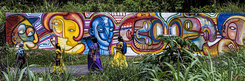 A colorful mural in Boquette, Panama with Indigenous folks, in very colorful clothing walking along in front of it.
