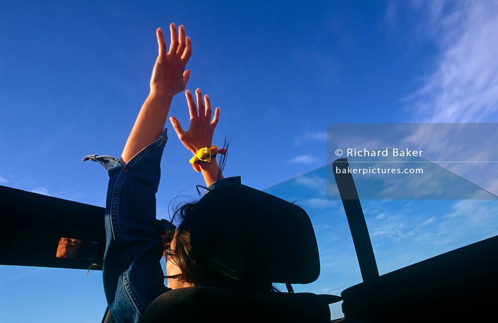 A woman car passenger holds her hands up high, into the oncoming wind of a fast open-time car.