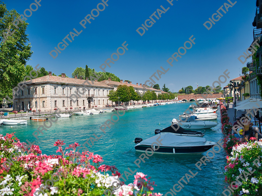 Boats parked along the peschiera del garda canal in Lake Garda, Italy during a summer afternoon with clear skies