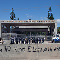 Riot police laying seige to the National University of Honduras battle with students protesting the assassination of Berta Cáceres. The graffiti blames the State for killing her.