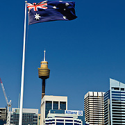 Australian flag flying in the breeze with Sydney's Centrepoint tower and other buildings in Sydney's CBD