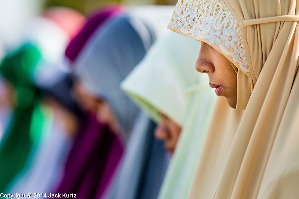 28 JULY 2014 - KHLONG HAE, SONGKHLA, THAILAND: A woman prays during Eid at Songkhla Central Mosque in Songkhla province of Thailand. Eid al-Fitr is also called Feast of Breaking the Fast, the Sugar Feast, Bayram (Bajram), the Sweet Festival and the Lesser Eid, is an important Muslim holiday that marks the end of Ramadan, the Islamic holy month of fasting.   PHOTO BY JACK KURTZ