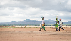 30 May 2019, Mokolo, Cameroon: People walk towards the Minawao camp for Nigerian refugees, from Mayo Luguéré ('River Muguéré). The Minawao camp for Nigerian refugees, located in the Far North region of Cameroon, hosts some 58,000 refugees from North East Nigeria. The refugees are supported by the Lutheran World Federation, together with a range of partners.