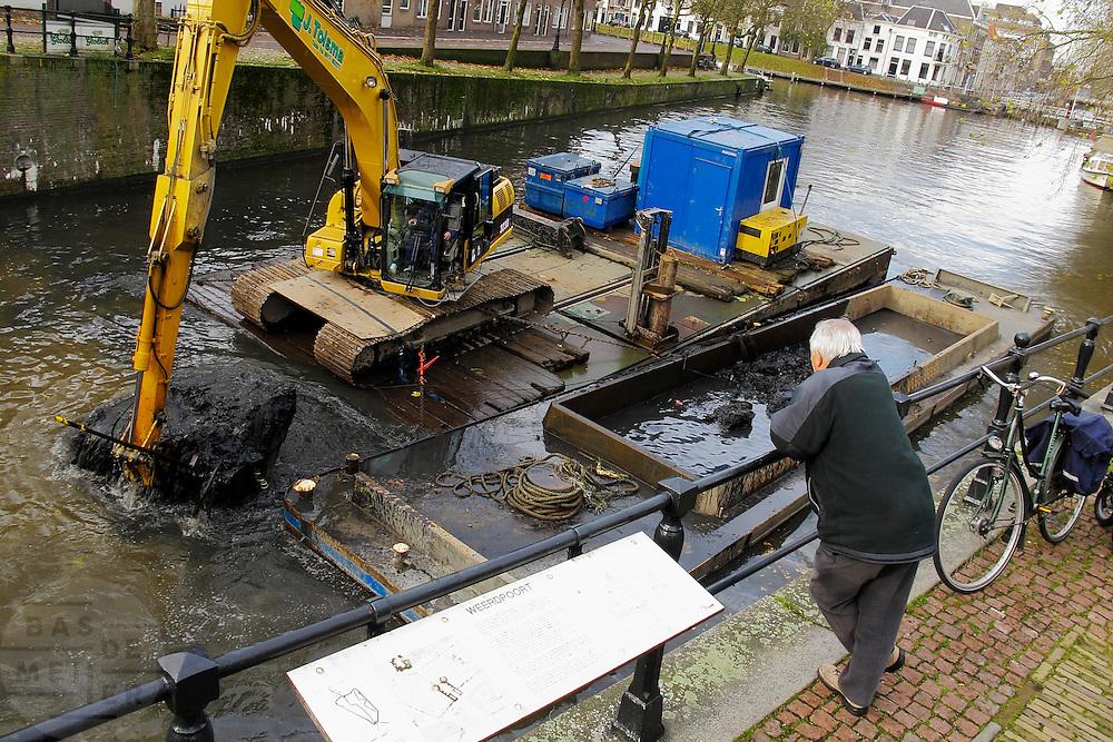 Een man kijkt naar baggerwerkzaamheden in de grachten van Utrecht.<br /> <br /> A man is looking at the dredging in the canals of Utrecht.