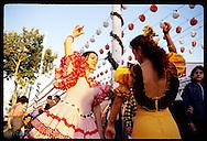 Two women in flamenco dresses dance an impromptu sevillana during Feria de Abril; Seville. Spain