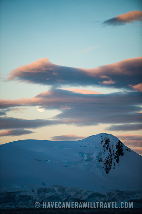 The moon rises over a mountain at sunset at Paradise Harbor, Antarctica. In summer there is close to (or actually, depending on how close to the pole and how close to the summer solstice) 24 hours of daylight, so even when the sun does set it remains quite bright during a few hours of twilight before the sun rises again.