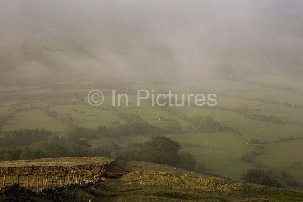 From a hillside overlooking this beautiful and idyllic pastoral landscape, early morning mist spreads across the Vale of Edale, in the Peak District National Park, Derbyshire. Edale is a valley in North Derbyshire, situated about 15 miles west of Sheffield, a loose collection of scattered farmsteads or 'booths' as they are known which grew up around the original shelters or 'boothies' used by shepherds when tending their sheep on the hillsides. There are 5 main ones in Edale valley, Nether Booth, Ollerbooth, Upper Booth, Barber booth and Grindsbrook Booth of which the village called Edale is part. Edale village is in a lovely setting below Kinder Scout and is the start of the Pennine way, the first and longest footpath in England, opened in 1965.