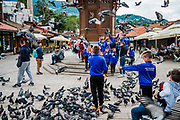 A visiting boys soccer team nd other tourists try and take photos among the pigeons near the Sebilj which is a pseudo-Ottoman-style wooden fountain in the centre of Baščaršija square in Sarajevo's Old Town.