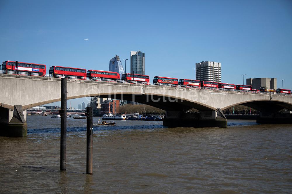 Traffic jam line of red London buses in a queue to cross Waterloo Bridge in London, England, United Kingdom.