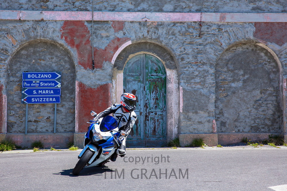 Motorcyclist on Suzuki R GSX motorbikes drives The Stelvio Pass, Passo dello Stelvio, Stilfser Joch, to Bormio, Italy