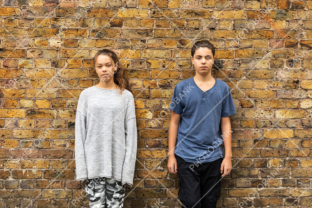 Portrait of a couple of tennagers with the background of a brown brick wall in an urban context. Exterior