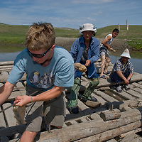 Members of an archaeology expedition help to pull a wooden ferry across a river between Rinchenlhumbe and Tsaagan Nuur in northern Mongolia's Darhad Valley.