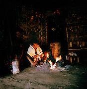 Young boy preparing coffee in traditional Dorze hut, Dorze region, South West Ethiopia.