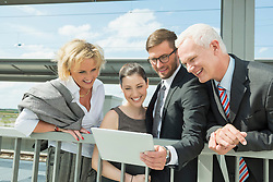 four business partners looking at tablet computer