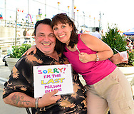 """Brooklyn, New York, USA. 10th August 2013. LARRY MCGOWAN is holding a sign """"Sorry, I'm the last person on line"""" that volunteer artist LAURA YORBURG uses when painting designs on visitors during the 3rd Annual Coney Island History Day celebration."""