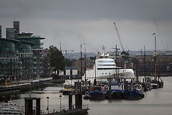 © Licensed to London News Pictures. 10/09/2016. LONDON, UK.  Motor Yacht A leaves London under Tower Bridge on the River Thames early this morning and is seen passing the historic Hermitage Moorings in Wapping. The £225m superyacht, owned by Russian billionaire, Andrey Melnichenko (known as the King of Bling) has spent the last week moored next to HMS Belfast during a London visit. Motor Yacht A is 390ft long, was designed by Philippe Starck, inspired by a submarine and is now reported to be up for sale because Melnichenko is building a new superyacht.  Photo credit: Vickie Flores/LNP