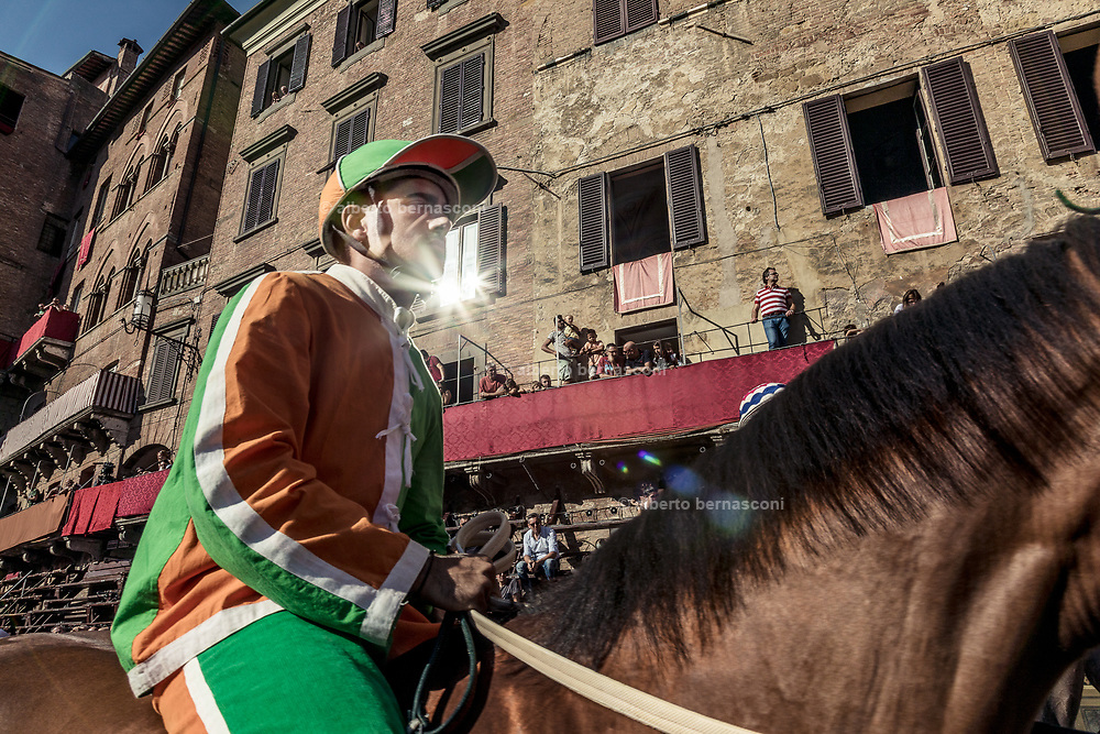 """Italy, Siena, the Palio: preparing for the  trial called """" Provaccia"""" , the bad trial, for the lack of enthuasiasm shown by the jockeys who spare the horses for the demanding evening race After this test, captains and jockeys gather at the City Hall to enscribe the jockey and show his colors. After this the jockey can no longer be changed."""