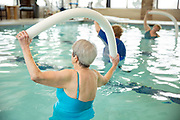 Senior women doing water aerobics in pool with pool noodle