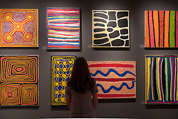 © Licensed to London News Pictures. 29/06/2016. London, UK.  A woman views vividly coloured aboriginal contemporary art on the JGM Art stand at the preview, in Chelsea, of Masterpiece London, the leading international fair for art and design from antiquity to the present day with works from 154 world-renowned exhibitors on sale.  The fair is open until 6 July.Photo credit : Stephen Chung/LNP