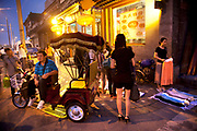 Rickshaw driver waits in the evening light at the entrance to Yandaixiejie Street (meaning Tobacco Pipe Lane) in Beijing, China. Located near to Houhai in downtown Beijing, Yandai Xiejie Street is a Hutong which attracts many tourists at day and night to it's souvenir shops and towards the bar area it leads to.