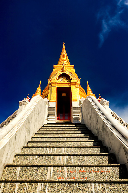 The Climb: An unusual view looking up a long set of stairs that lead to a deep gold coloured Stupa set against a vivid deep blue sky, Tritotsathep Temple, Bangkok Thailand.