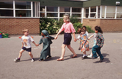 Multiracial group of junior school children and teacher holding hands in playground,