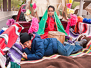 """03 DECEMBER 2011 - PHOENIX, AZ:    A boys lays in the bed of a pickup truck while his sister portrays the Virgin of Guadalupe in a procession in Phoenix Saturday. The Phoenix diocese of the Roman Catholic Church held its Sixth Annual Honor Your Mother Day Saturday to honor the Virgin of Guadalupe. According to Mexican Catholic tradition, on December 9, 1531 Juan Diego, an indigenous peasant, had a vision of a young woman while he was on a hill in the Tepeyac desert, near Mexico City. The woman told him to build a church exactly on the spot where they were standing. He told the local bishop, who asked for some proof. He went back and had the vision again. He told the lady that the bishop wanted proof, and she said """"Bring the roses behind you."""" Turning to look, he found a rose bush growing behind him. He cut the roses, placed them in his poncho and returned to the bishop, saying he had brought proof. When he opened his poncho, instead of roses, there was an image of the young lady in the vision. The Virgin is now honored on Dec 12 in Catholic churches throughout Latin America and in Hispanic communitied in the US.   PHOTO BY JACK KURTZ"""