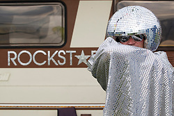 """© Licensed to London News Pictures . 24/08/2012 . Leeds , UK . Paul Burman (aka """" Disco Balls """") from Newcastle soaks up the sun outside his camper van at the Leeds Festival in Bramham Park . Photo credit : Joel Goodman/LNP"""