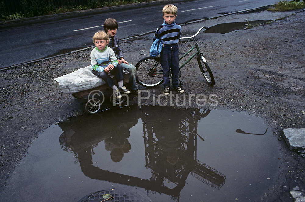 Children play near a puddle in the town of Nova Huta. In filthy industrial streets, the kids look undernourished in this scene of impoverished, Communist dereliction. It is horribly depressing and unhealthy place to grow up and these children are pale and yet seem happy, with smiles on their faces. The famous steel works can be seen reflected in the puddle before them. After the war, Stalin decided to build an industrial Communist fantasy just outside Krakow: a model town and immense steelworks of the future. The steelworks was named after Lenin and the town would be called Nowa Huta  - or, the new steel mill. At its peak, 27,000 people worked at the Lenin Steelworks. But Solidarity grew strong forcing strikes over pay and recognition over their union. Today, it is an economic and ecological disaster area.