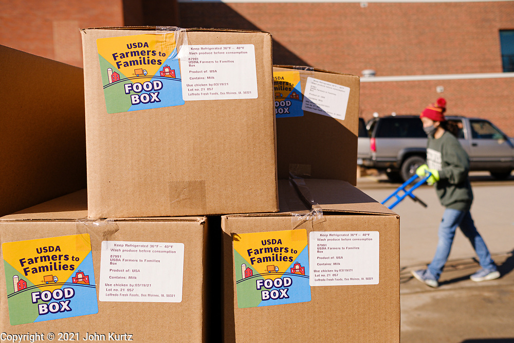 "27 FEBRUARY 2021 - DES MOINES, IOWA: A volunteer pushes a hand truck past a stack of food boxes during an emergency food distribution at the John R. Grubb Community YMCA in Des Moines. The food distribution was organized by Farmers to Families and the YMCA. They had 1,000 boxes of emergency rations which included fresh fruit and vegetables, yogurt, chicken and hot dogs. They also had 1,000 gallons of milk. The neighborhood around the YMCA is a ""food desert,"" with no nearby grocery stores that sell healthy food. Food bank use in Iowa is up more than 60% since the start of the Coronavirus pandemic. Food bank officials estimate that 4 in 10 users are new users of emergency food pantries.       PHOTO BY JACK KURTZ"