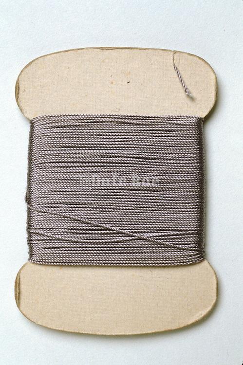still life of a flat carton spool with yarn