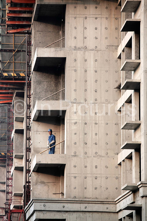"""A worker mans a drill at an unfinished apartment  complex in Shanghai, China on 29 December, 2009.  China has tightened land-sale regulations for developers in its latest attempt to take some of the steam out of the potentially overheating property market, this followed a recent vow from Beijing last week to curb what it calls an """"overly fast"""" rise in property prices by boosting the supply of cheap public housing and redeveloping slum areas.."""