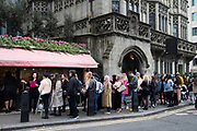 Queue of people waiting outside the Elan Cafe on Park Lane in London, England, United Kingdom. This exclusive little place is one of the places to be in London, famed for its style and cakes.