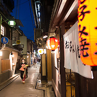 A young maiko walks down a tiny pedestrian lane in the Pontocho neighborhood of Kyoto, Japan.