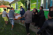 A coffin containing a deceased Roma man is carried into the family yard and towards the entrance of his home in the village of Valea Seaca in Bacau County, Romania, while closely related women cry out their grief. Inside the house the lid will be taken off, so that family and friends can spend time with the deceased during the wake which will go on for three days.