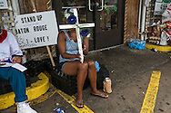 Woman mourning Alton Sterling in front of the Triple S convience store where police shot and killed him.