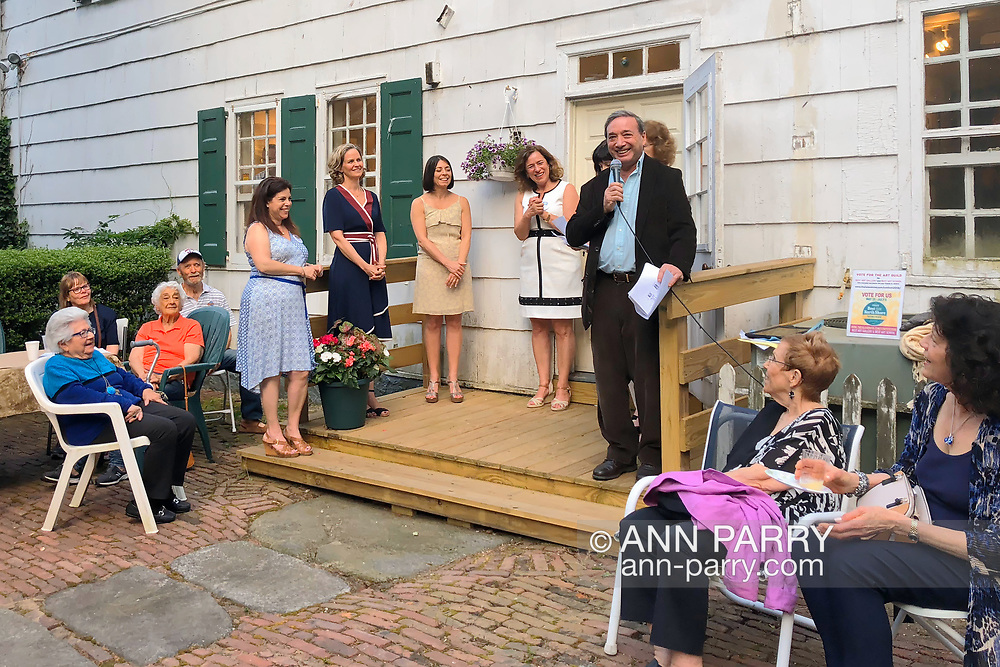 Manhasset, New York, U.S., June 8, 2018. Juror MARC JOSLOFF (holding mic) speaks - with Nassau County Executive LAURA CURRAN (in navy blue dress) and TAG Board Members to left of Josloff, during Award Ceremony during Reception for The Art Guild exhibition held at historic Elderfields Preserve. Sitting to right of Josloff are (l-r) JUDI FEINMAN and SUSAN SILKOWITZ.