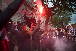 © Licensed to London News Pictures. 06/06/2020. London, UK. Protesters light a flare as they gather in Westminster, central London to take part in a Black Lives Matter demonstration over the killing of African American George Floyd. The death of George Floyd, who died after being restrained by a police officer In Minneapolis, Minnesota, caused widespread rioting and looting across the USA. Photo credit: Ben Cawthra/LNP