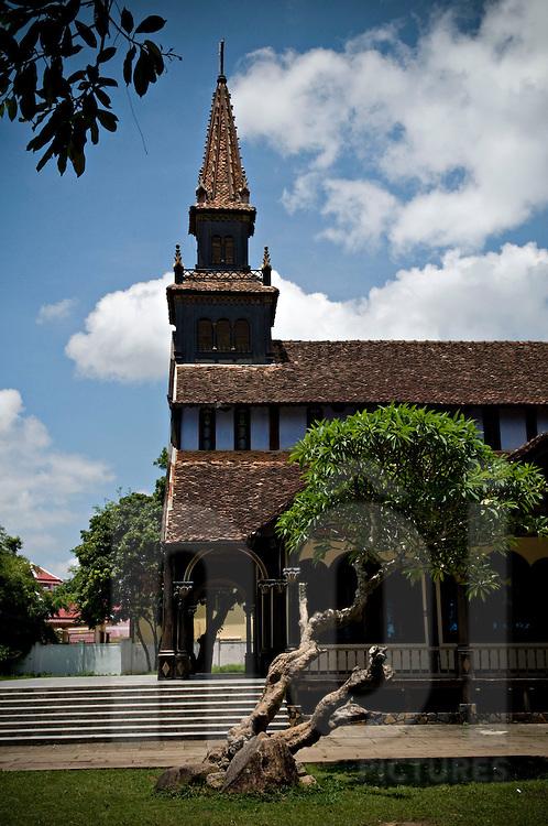 Side view of Kontum's catholic church, Vietnam, Asia. Bell tower raises to the cloudy sky. Vietnam, Asia