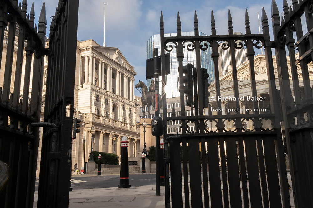 Days before the Chancellor Rishi Sunak delivers his Budget, a wide view of the Bank of England and the statue of a mounted Duke of Wellington, are seen through the half-open gates of an entrance to Bank Underground Station in the City of London, the capital's financial district, on 1st March 2021, in London, England.